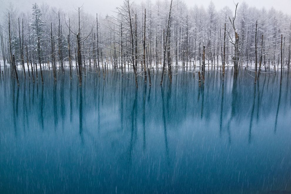 "12. ""Blue Pond during the May snowfall."" This place attracts tourists from all over the world. The settlement Biei, Hokkaido, Japan. (Kent Shiraishi / National Geographic Traveler Photo Contest)"