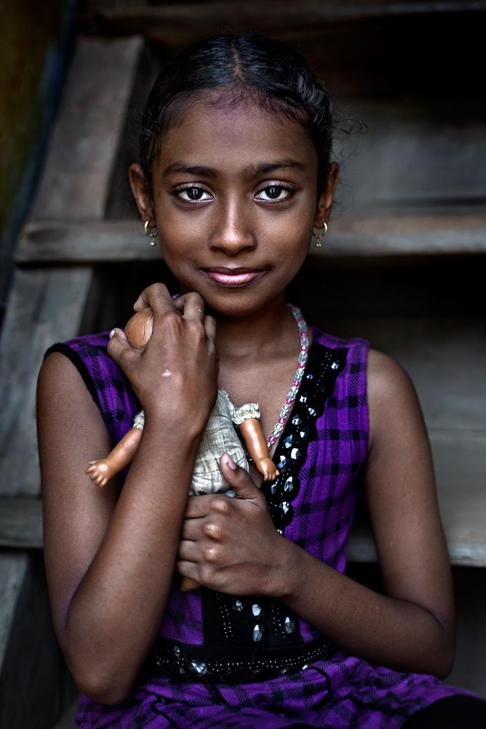 "32. ""Portrait of a Girl."" Portrait of a girl with a doll from a poor neighborhood in Fort Cochin, Kerala, India. (Bruno Tamiozzo / National Geographic Traveler Photo Contest"