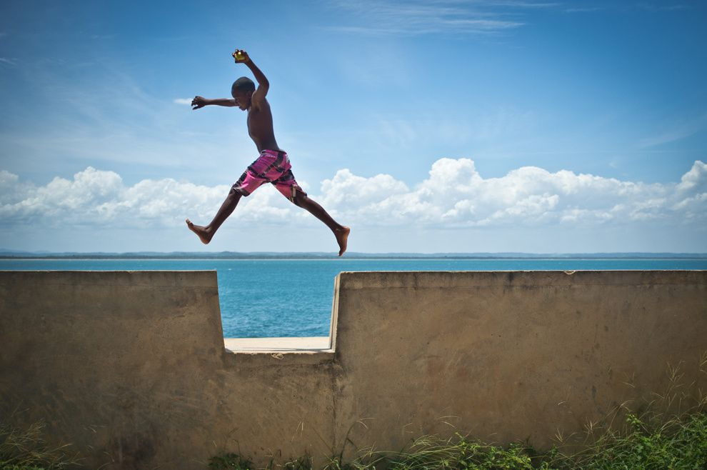 "24. ""The soul of the child."" A boy jumps over the recess in the 500-meter-high fortress wall. Morro de Sao Paulo, Bahia, Brazil. (Mauricio Pisani / National Geographic Traveler Photo Contest)"