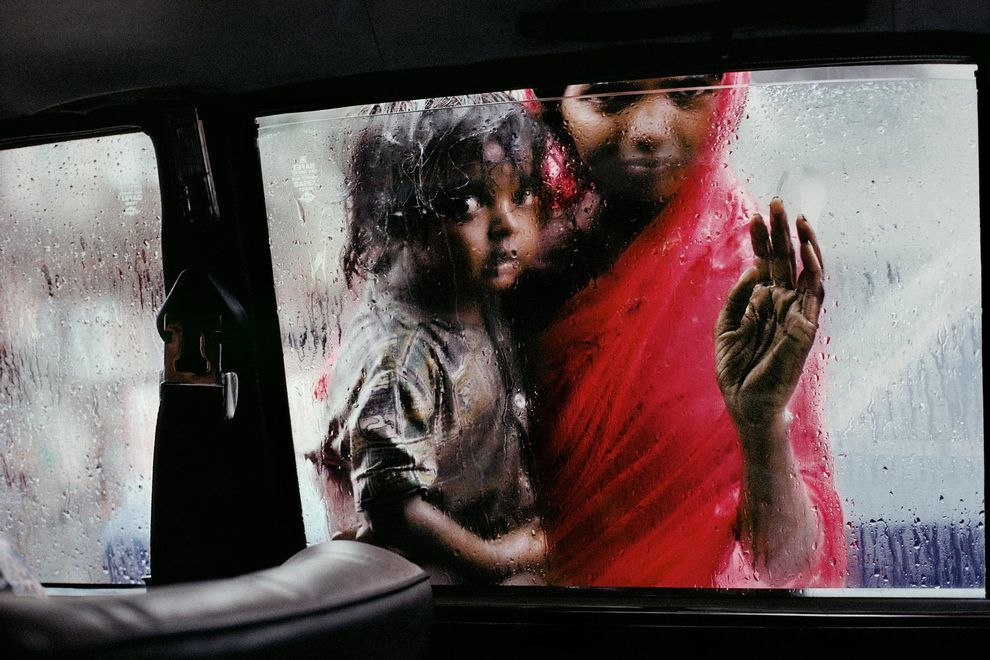 Mother with a child looking out the window a taxi in Bombay, India, in 1993 (by Steve McCurry)