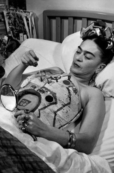Frida Kahlo in a hospital bed, drawing on her cast with the help of a mirror, 1951