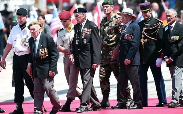 WWII veterans are escorted by soldiers as they arrive at the International Ceremony at Sword Beach