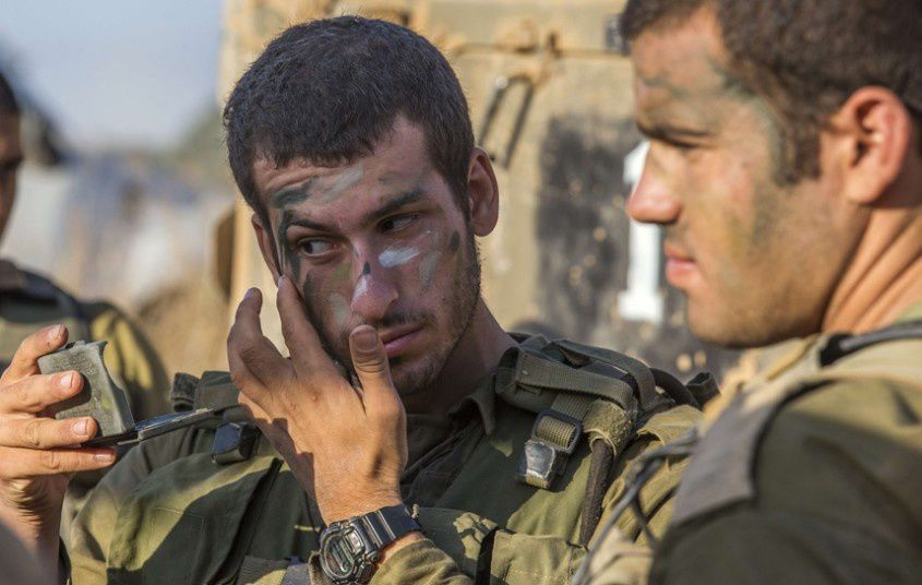 Israeli soldiers camouflage their faces at an army staging area along Israel's border with the Gaza Strip