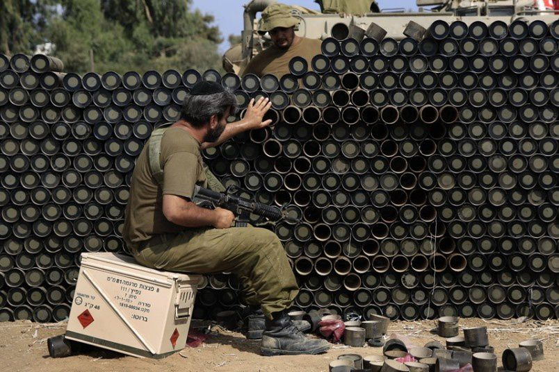 An Israeli reserve soldier makes a wall with the Star of David from cardboard mortar shell boxes near the Israel Gaza border