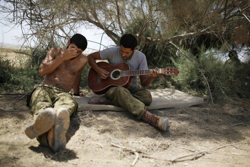 An Israeli soldier plays a guitar at a staging area near the border with Gaza