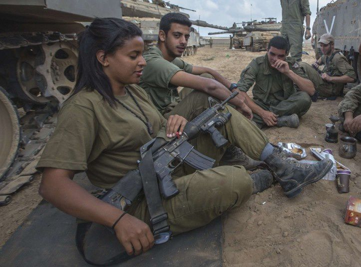 A female Israeli soldier holds her weapon as she takes a rest with her comrades at an army deployment near the Israeli-Gaza border