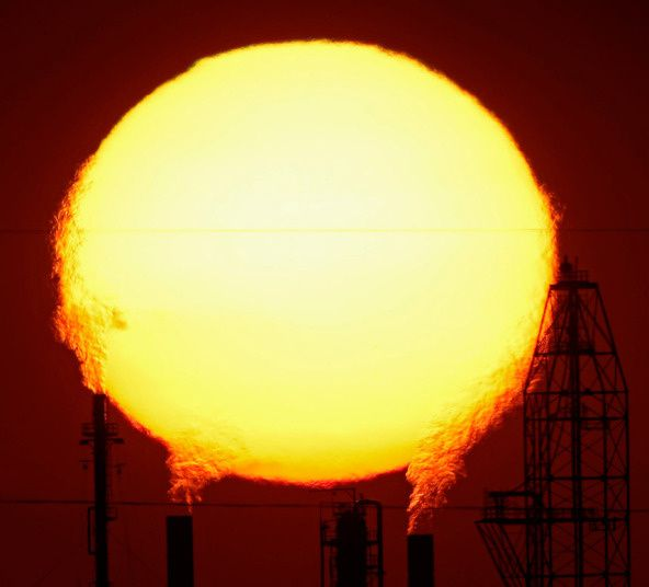 The sun sets behind the National Cooperative Refinery Association oil refinery in McPherson, Kansas