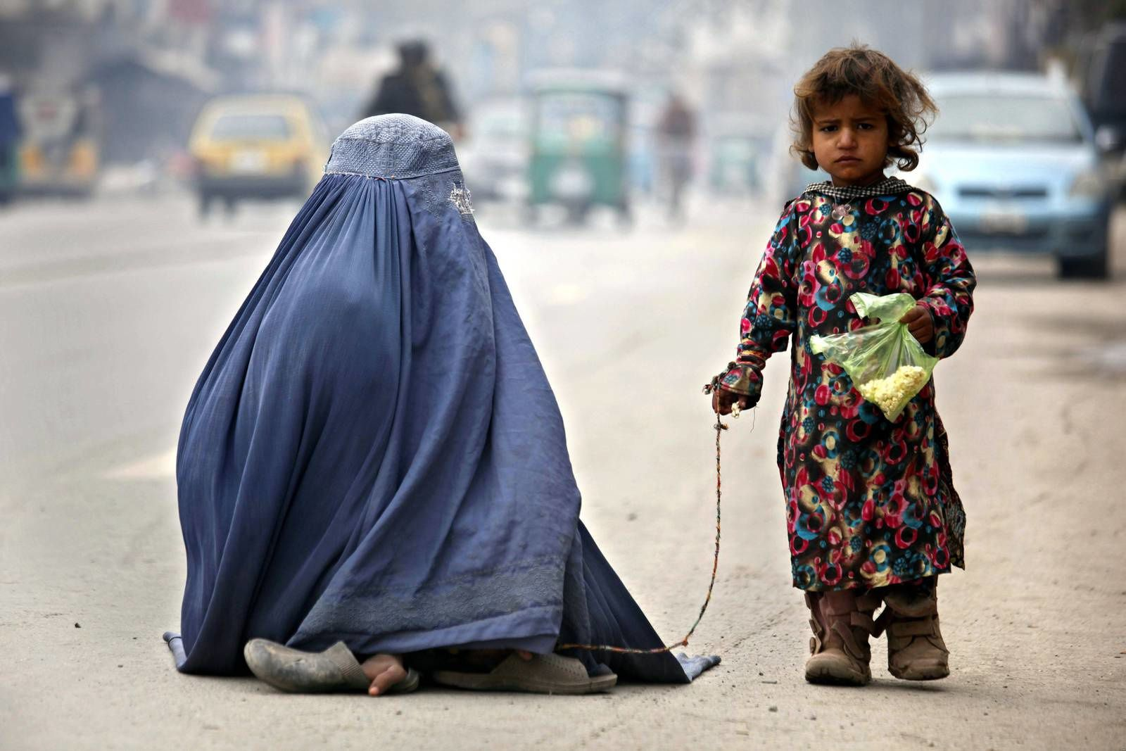 A mother and her daughter begs for alms on a road in Peshawar, Pakistan