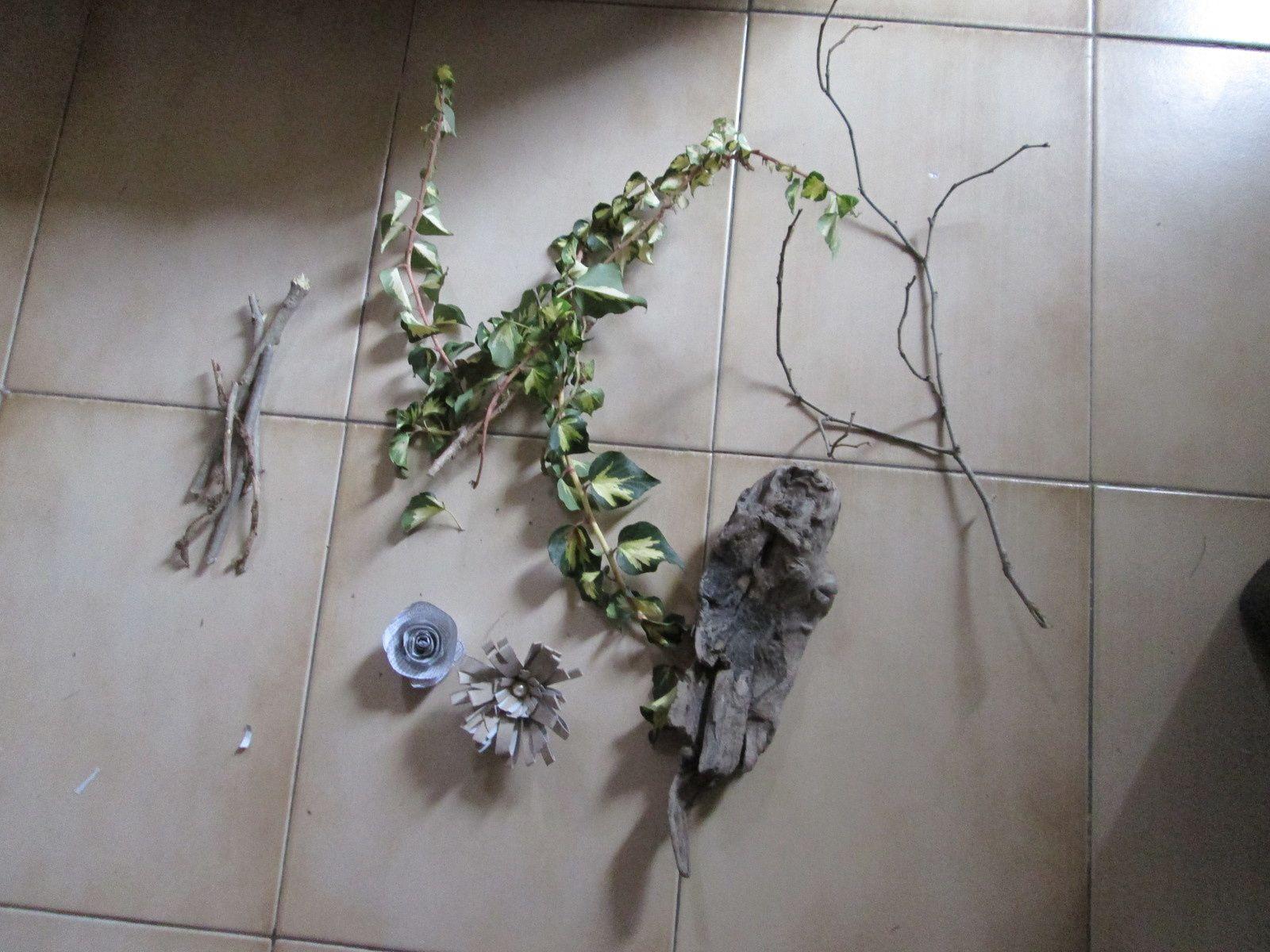 Un morceau de bois flotté que j'ai huilé, une branche morte, des petits bouts de bois pour faire un buchet, une fleur en carton, des fleurs en papier et du lierre
