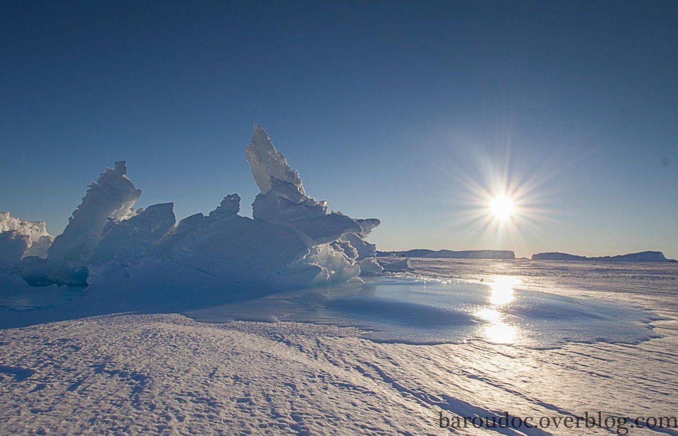 La petite étendue d'eau visible est bel et bien une plaque de glace au pied du berg, témoin d'une résurgence (remontée d'eau au-dessus de la banquise).