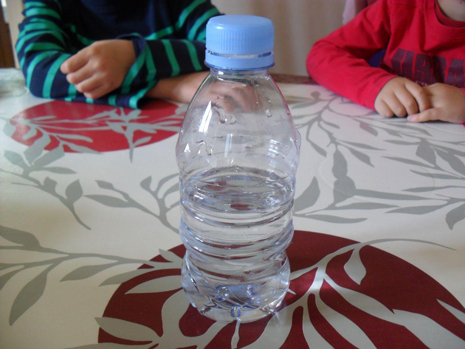 Observer une bouteille d'eau qui n'est pas complètement remplie : l'air reste toujours en haut, car il est plus léger que l'eau.
