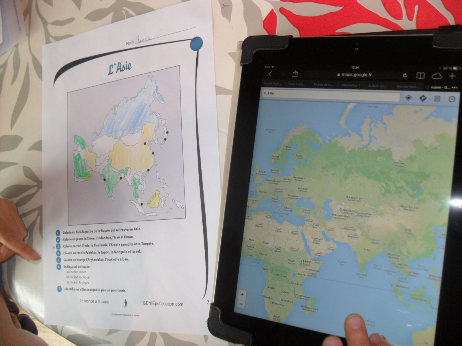 """Lucas travaille sur une fiche sur l'Asie avec """"le monde à la carte"""" de chez Génie Publications. Il fait des recherches sur l'Ipad pour répondre aux questions."""
