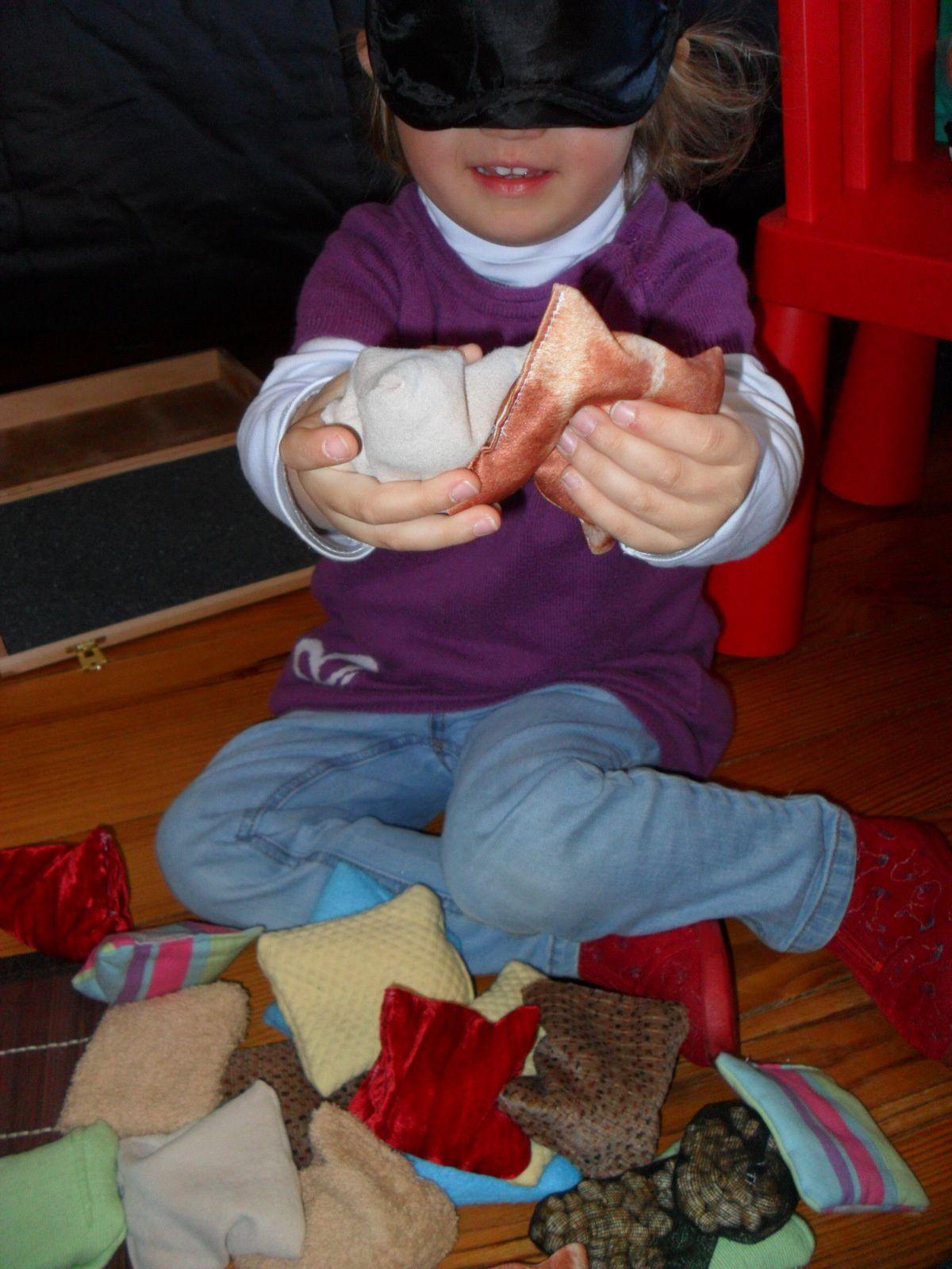 Elle prend un coussin dans sa main droite, et un cousssin dans sa main gauche et les touche pour regarder s'ils sont identiques.