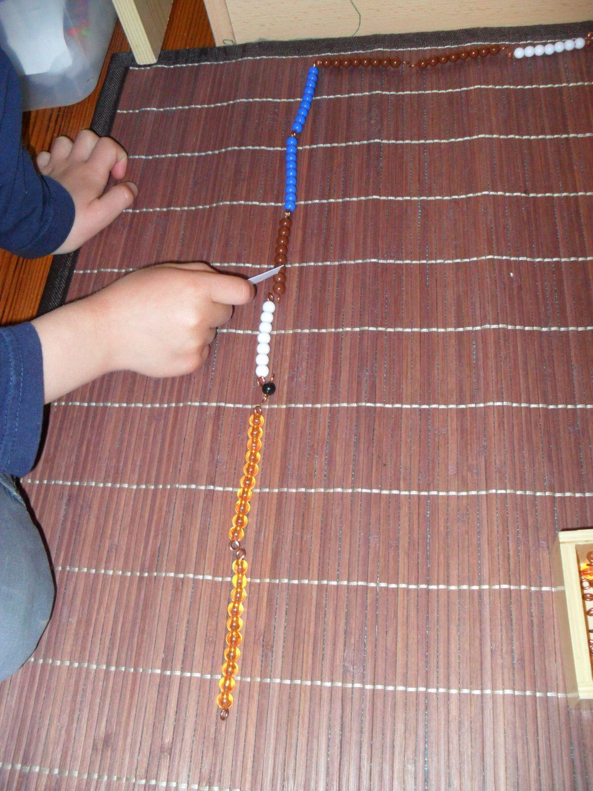 Mathieu compte les perles et quand il arrive à 10, il met sa cale blanche et transforme ses perles : les 10 perles comptées en barrette dorée et le reste en barrette noire et blanche.