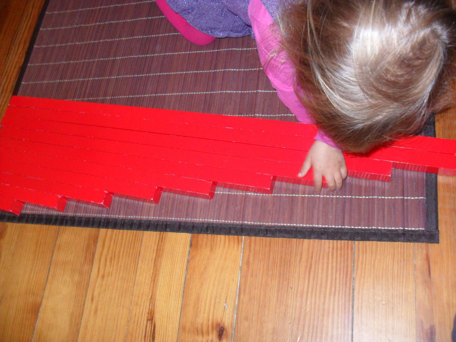 Elle vérifie son travail en faisant glisser sa main sur les barres rouges.