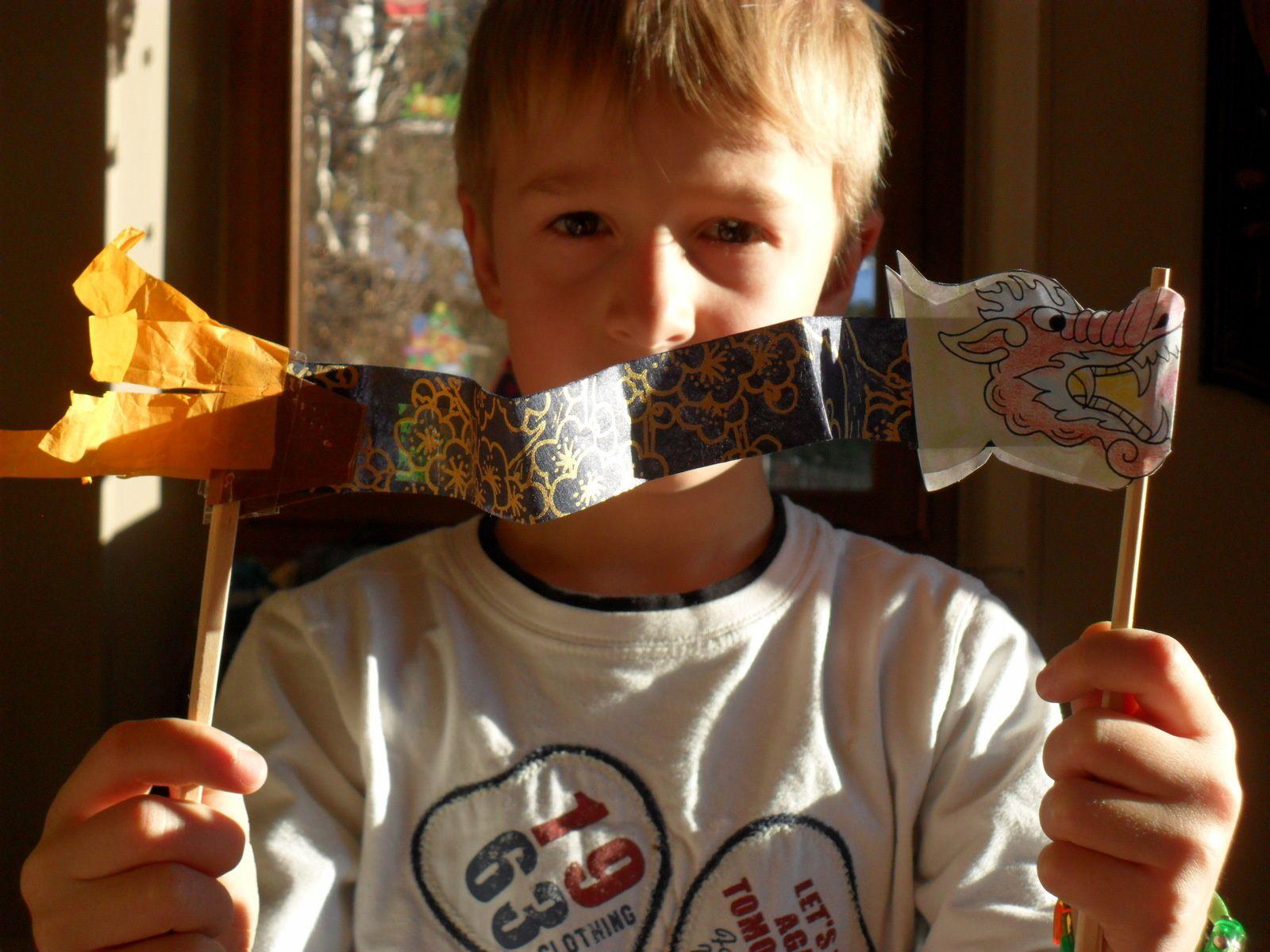 """Assembler la queue du dragon avec une deuxième baguette en bois, lui ajouter des """"franges""""."""