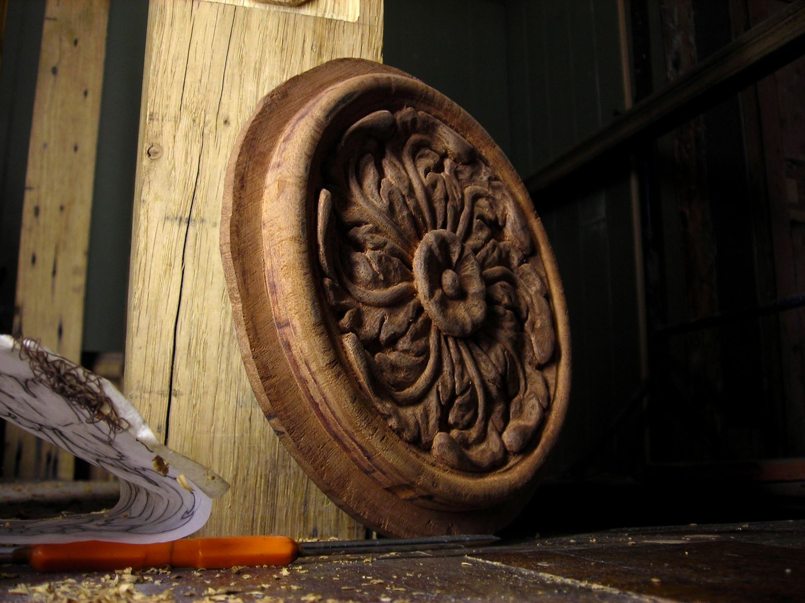 Une rosette en acajou qui sera sertie dans un panneau vouté.