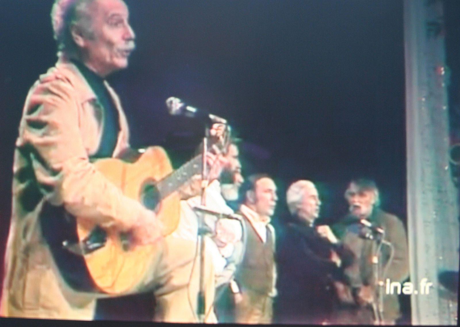 """En décembre 1979, Georges Brassens chante """"Le roi des cons"""" avec un choeur constitué de Maxime Le Forestier, Georges Moustaki, François Béranger, Marcel Amont et François Cavanna (à droite) qui reprend le refrain :. """"Il y a peu de chances qu'on détrône le roi des cons""""."""