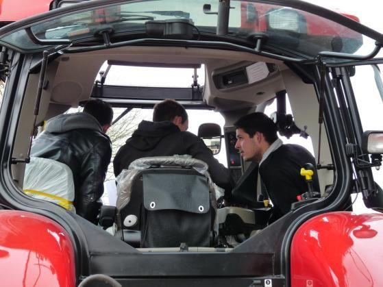 Les stagiaires partagent leurs expériences sur l'utilisation des différentes commandes dans une  cabine de tracteur afin de calibrer la transmission après sa maintenance.