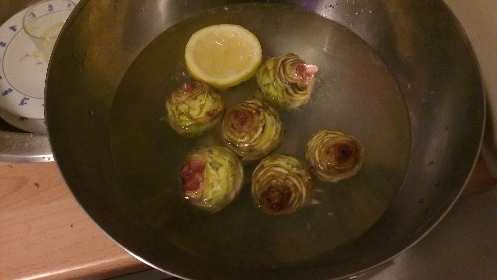 """""""Tourner"""" les artichauts, c'est-à-dire retirer toutes les feuilles en conservant le coeur. Couper la queue à 3 cm du coeur et l'éplucher sur 2 mm, puis """"tourner"""" avec le couteau autour du coeur de l'artichaut pour enlever la base des feuilles qui restent. Plonger les artichauts dans l'eau citronnée (pour éviter qu'ils noircissent, et d'une pierre deux coups les imbiber un peu de citron)."""