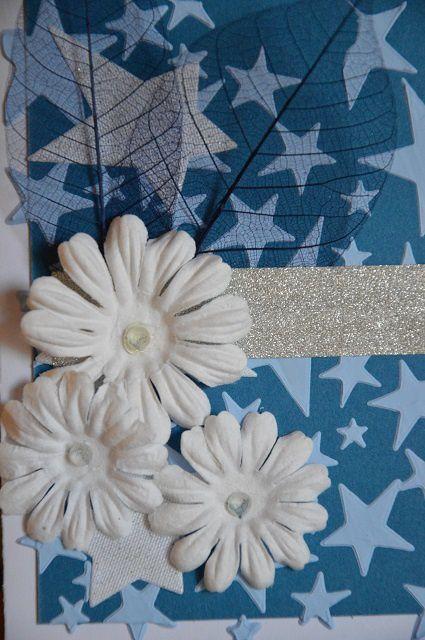 Pour finaliser la carte, j'ai collé 2 feuilles bleues foncées sur la 2e étoile en partant du bas. J'ai camouflé leur base à l'aide d'un masking tape argenté et pour donner du relief j'ai mis 3 fleurs blanches en papier de 2 tailles différentes avec un strass opaque en leur centre (coeur de la fleur).