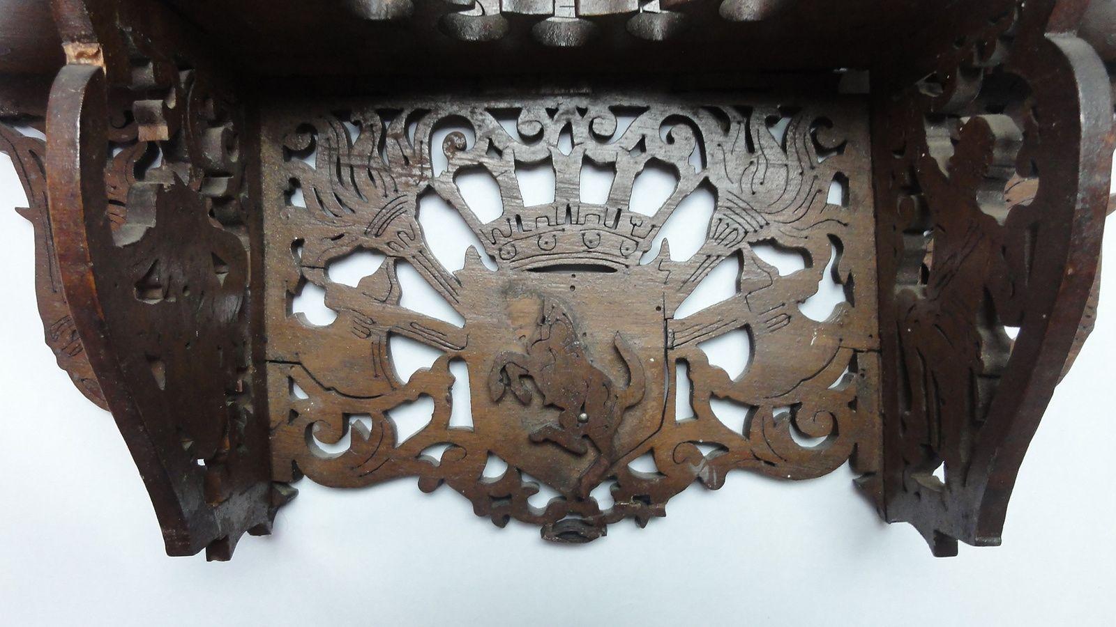 en dessous du plateau (partie centrale)  2 flambeaux , 2 haches et un blason sur lequel est apposé un cheval cabré (manque la tete)