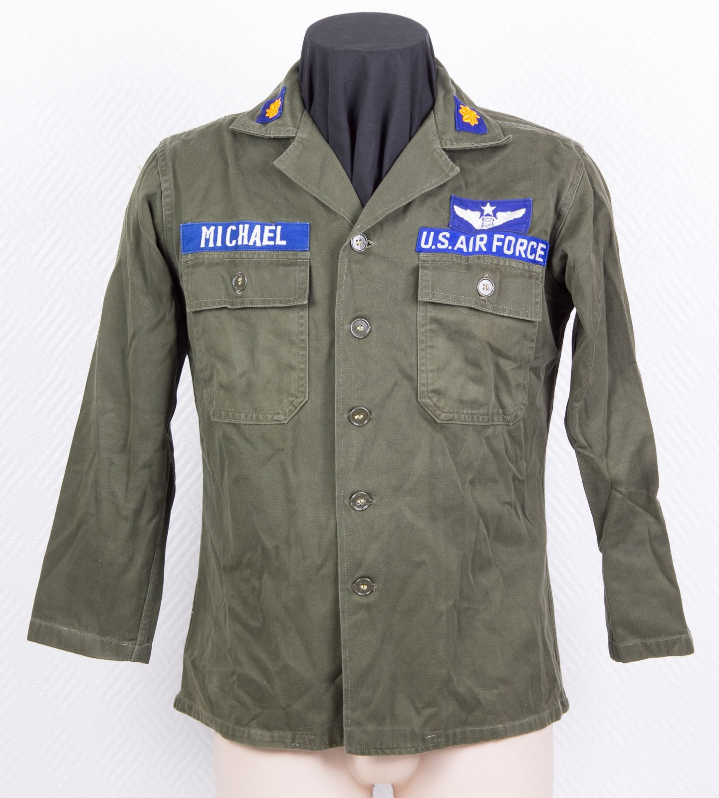 The grouping is a snapshot of what Maj. Michael wore while based at Korat RTAFB in 1975. The OG 107 utility uniform is surprisingly the outdated 1st model, easily identified with the rectangular flaps of the breast pockets. Full color patches are worn, including name and U.S. Air Force tapes, wings and ranks. Trousers and leather boots (not shown) also came with the grouping.