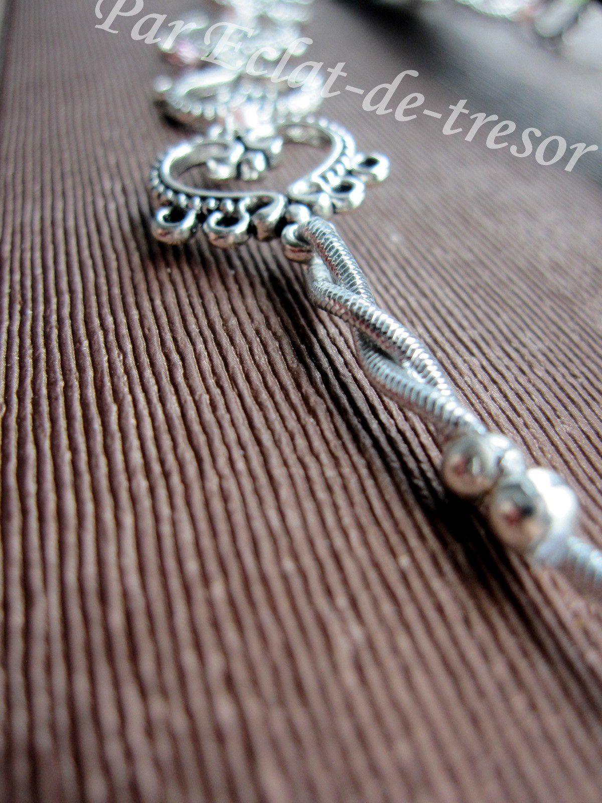 HEADBAND ENCHAINEMENT DE COEURS, PERLE ROSE NACRÉ - Accessoire indispensable de cet été, ce bijou de tête romantique s'adapte à toutes les têtes grâce à son élastique argenté.  Conçu avec des coeurs en métal argenté reliés par des perles rose nacré et des cristaux Swarovski améthyste clair. Longueur : 51cm (réglable). [VENDU]