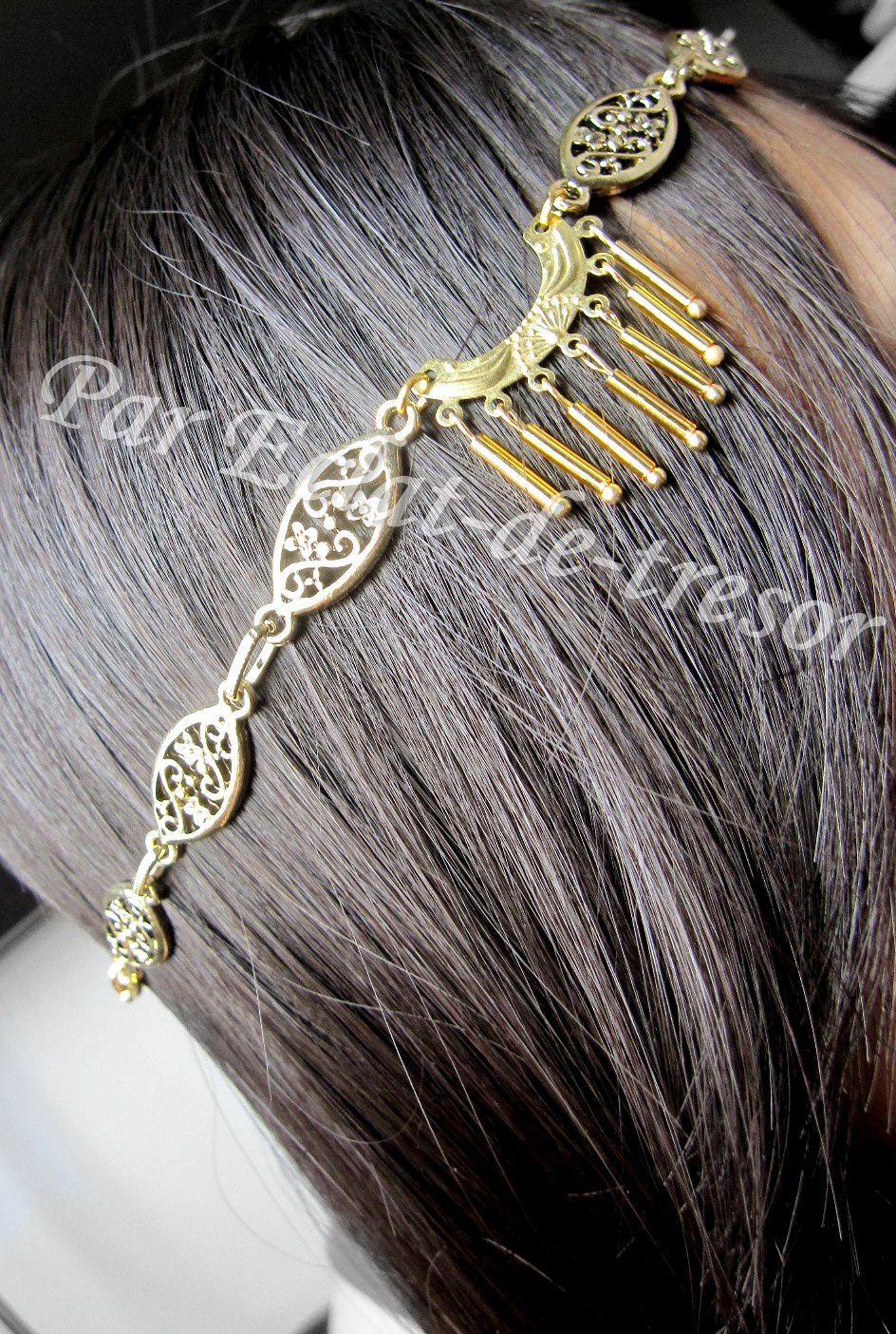 """HEADBAND COLLECTION DORÉ """"REINE"""" - Ce headband fera de vous la plus belle grâce à une chaîne formée de médaillons représentant des fleurs (en alliage de très belle qualité, finition dorée). Au centre des médaillons, un bijou au bout duquel pendent des tubes dorés vient ajouter un style à ce headband. Ce bijou de tête est conçu de façon à s'adapter à tout le monde grâce à son élastique (doré).  Longueur : 53,5cm (adaptable). [VENDU]"""