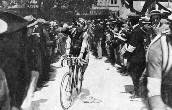 Gustave Garrigou slalome entre les nombreux spectateurs lors de l'édition de 1914, avec une chambre à air sur le dos. Béret et lunettes de protection de moto vissés sur la tête, il se désaltère (avec du vin ?). Grâce à son vélo équipé de deux pignons sur le moyeu avant – partie centrale d'une roue –, il atteint une moyenne kilométrique de 27, 32 km/h en 1911.
