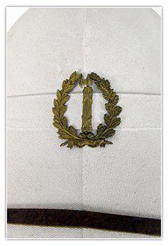 Les attributs d'uniforme des surveillants de bagne : insigne de casque colonial, pattes de col et boutons métaliques. Ils sont spécifiques et représentent le faisceau de licteur, symbole de la république.