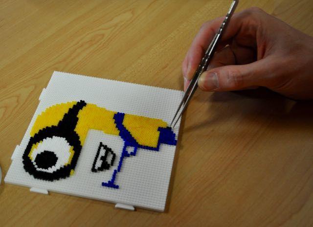 Un pixel Art en cours de construction . L'artiste utilse une pince pour placer les perles sur les picots