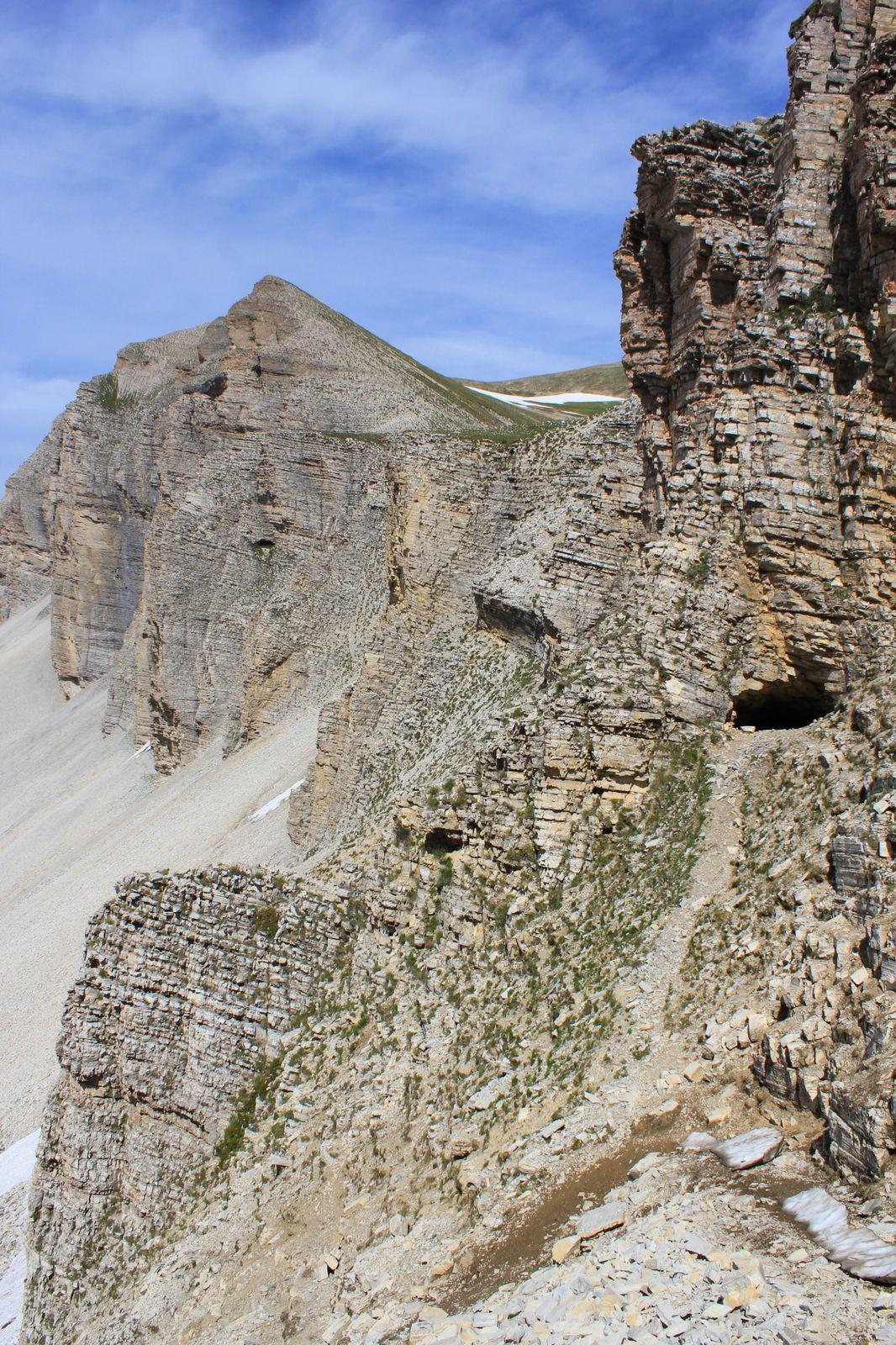 L'oeil de la Grotte, dans la rocaille, avec sa larme, sur fond de visage préhistorique. Au fond, la Tête du Lauzon