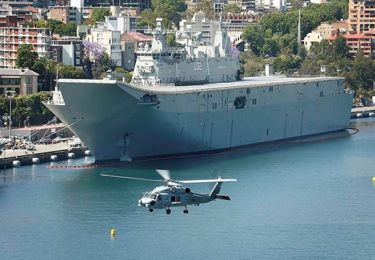 The Royal Australian Navy's latest helicopter, the MH-60R Seahawk, flies past the Navy's latest ship, HMAS Canberra in Sydney, NSW.