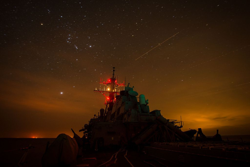 USS Mitscher (DDG 57) lights up its mast during night delayed landing qualifications.