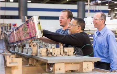 From left to right:  Sean Lockhart, Ali Khoshro start working on Canada's first wing of 2015 while Brent Miller, the Beam Shop Supervisor looks on.