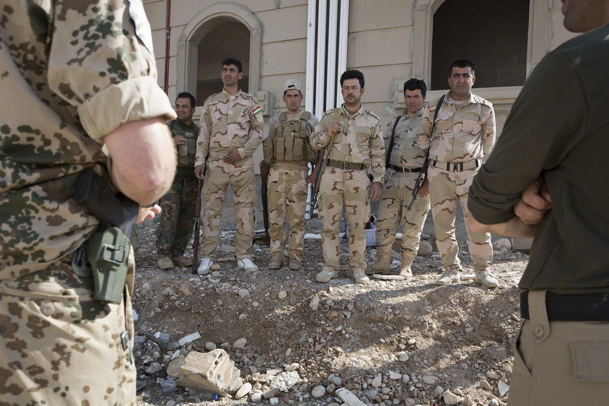 A German soldier, at left, speaks to a group of Peshmerga trainees through an interpreter, at right -  photo Matt Cetti-Roberts – WIB