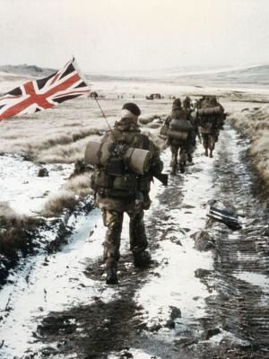 A column of 45 Royal Marine Commandos yomp towards Port Stanley. Royal Marine Peter Robinson, carrying the Union Jack flag on his backpack as identification, brings up the rear. This photograph, taken in black and white and colour, became one of the iconic images of the Falklands Conflict