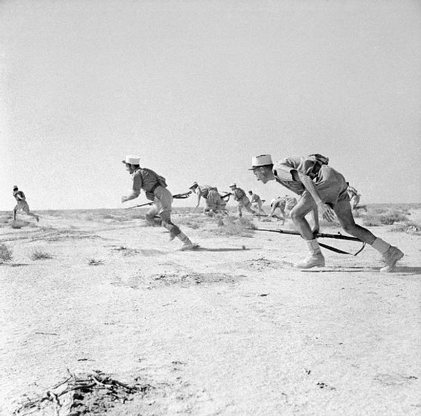Free French Foreign Legionnaires leap up from the desert to rush an enemy strong point, Bir Hakeim, June 1942