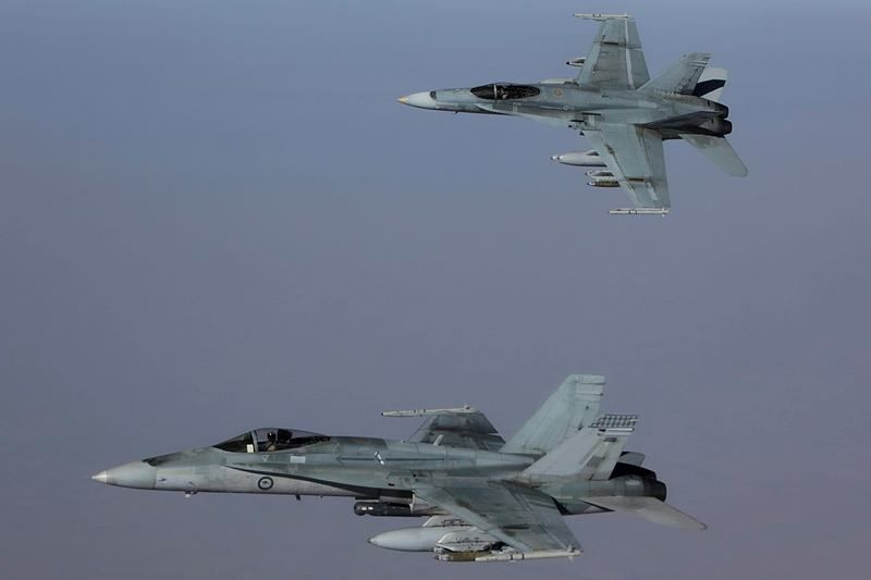 Two bomb-laden Royal Australian Air Force F/A-18A Hornet multi-role fighter aircraft formate on their tanker whilst transiting to Iraq for another mission. -  photo SGT Pete / Aus DoD