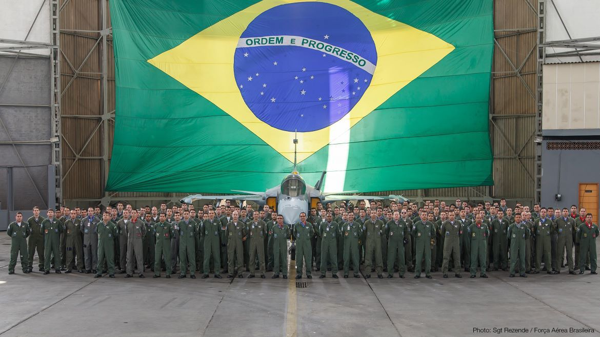 Brazilian air force pilots gathered in front of the Gripen full scale replica