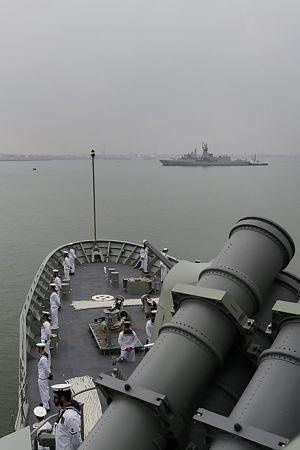 HMAS Stuart sailors stand at ease on the forecastle as they and HMAS Arunta prepare to come alongside in Zhanjiang, China
