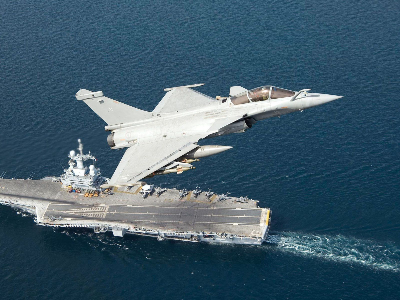 A French Dassault Rafale flies above the Charles de Gaulle aircraft carrier. photo Marine nationale.jpg
