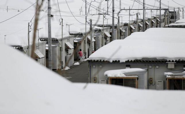 Photo prise le 17 février 2015 : femme habitant un ensemble de logements provisoire couvert de neige à Aizuwakama, dans la préfecture de Fukushima. Ce complexe abrite des réfugiés nucléaires d'Okuma, une ville située à l'intérieur de la zone d'exclusion autour de la centrale nucléaire de Fukushima Daiichi de TEPCO (Tokyo Electric Power Co.) REUTERS/Toru Hanai