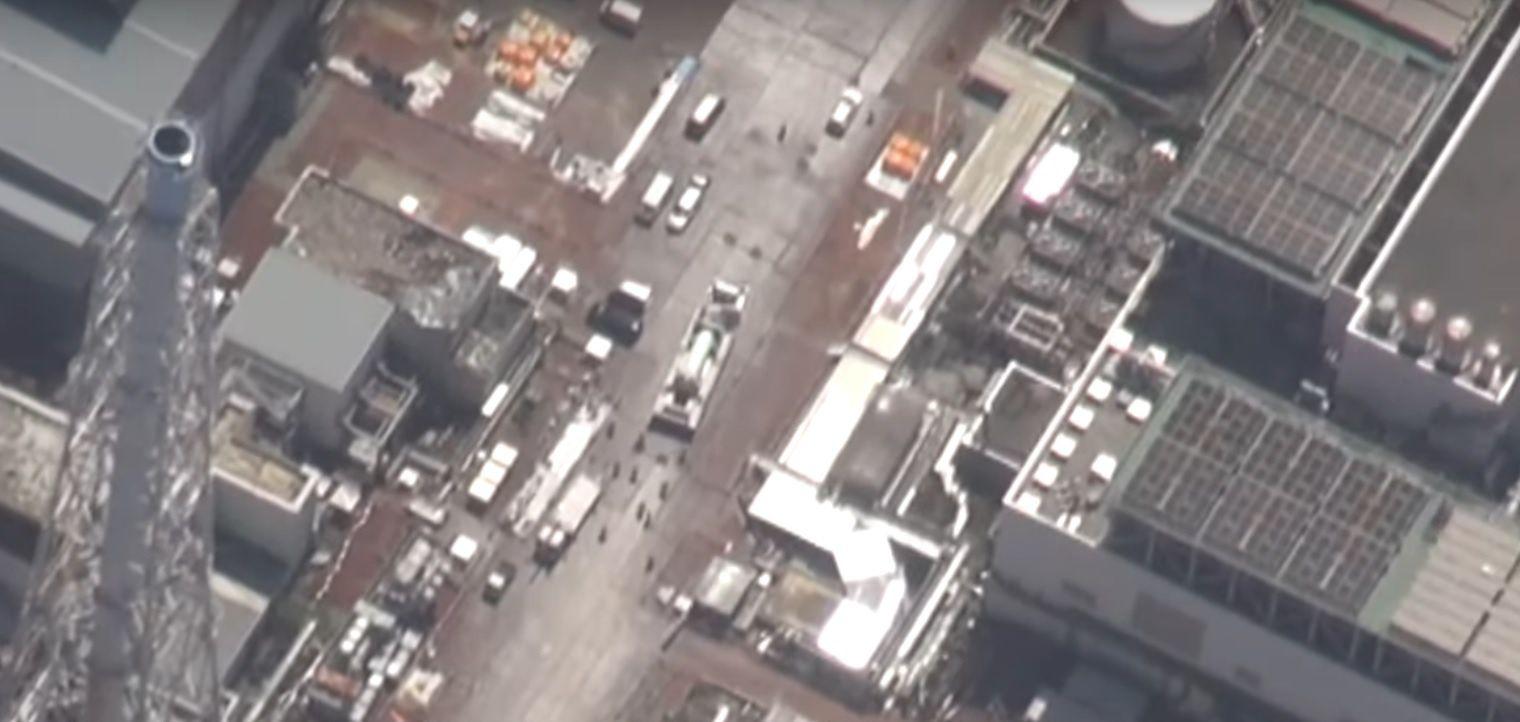 Le camion portant le conteneur s'approche de la piscine commune (capture vidéo aérienne Kyodo news).