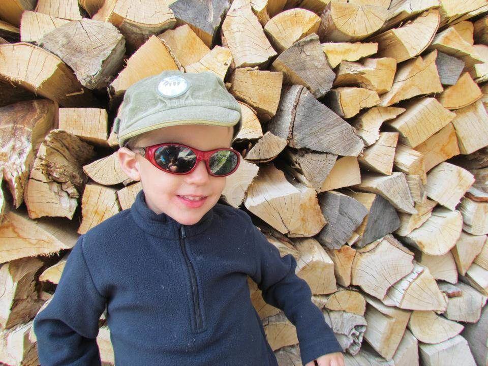 Corentin devant la réserve de bois du refuge