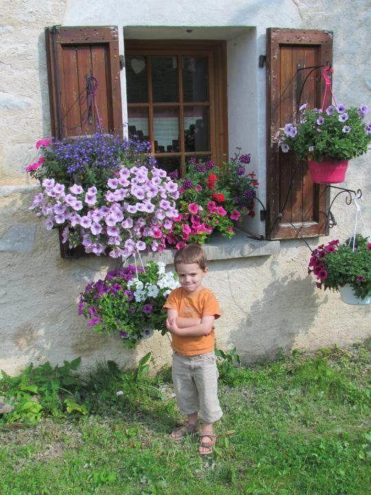 Corentin, devant l'auberge des Allières bien fleurie.