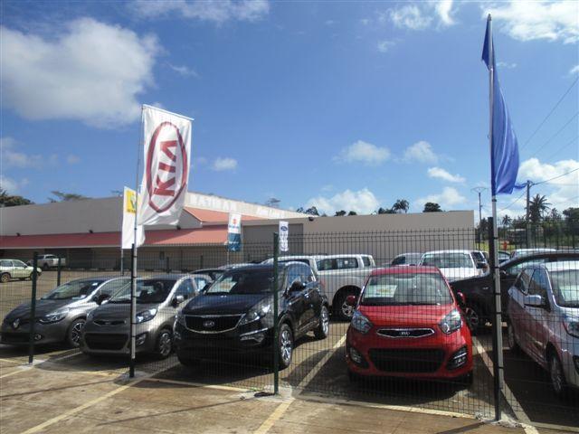 Le parking du fenuarama, avec le magasin citydia en arrière-plan, et la photo des voitures neuves à vendre.
