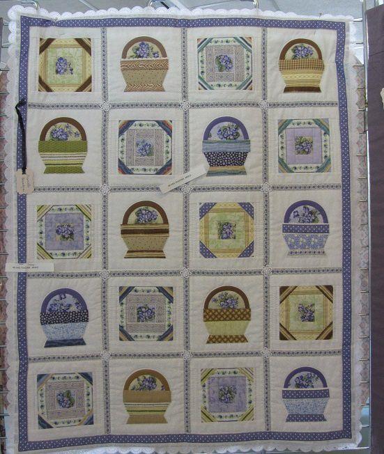 Petits paniers garnis de violettes, le tissu se retrouve dans le centre des blocs intermèdiaires. Le panneau est bordé d'une dentelle.