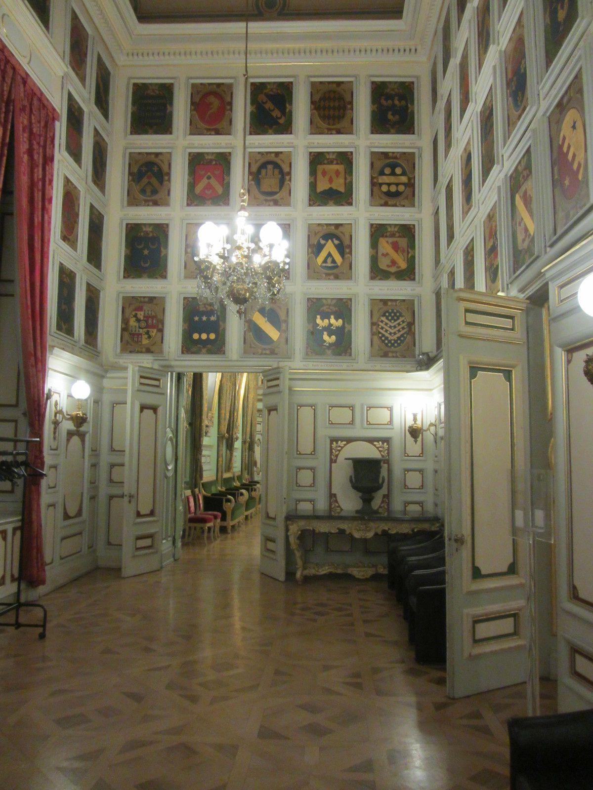 Voici la salle des armoiries, qui était à l'origine la salle des échevins. Leurs portraits ayant tous été brûlés, on les a remplacés pas leurs blasons.